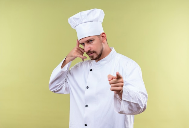 満足しているプロの男性シェフが白い制服を着て調理し、緑の背景の上に自信を持って立っている笑顔をジェスチャーと呼ぶジェスチャーを作る指でカメラを指している帽子を調理します
