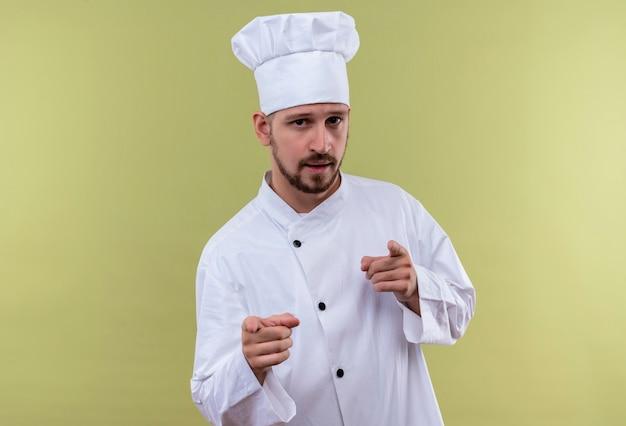 満足しているプロの男性シェフが白い制服を着て調理し、緑の背景の上に自信を持って立っているカメラを指で指している帽子を調理します。