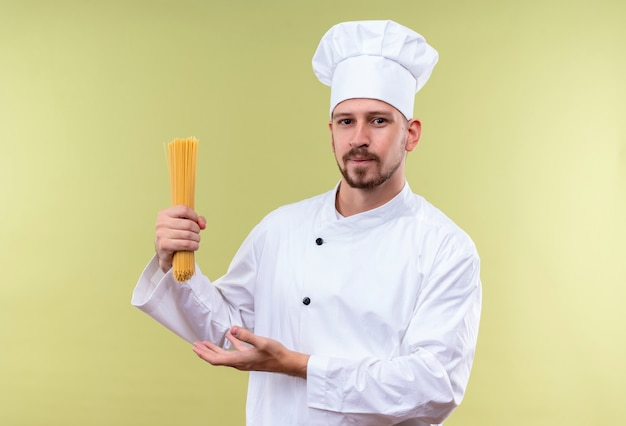 満足しているプロの男性シェフが白い制服を着て調理し、緑の背景の上に立っている生のスパゲッティパスタを提示する帽子を調理します。