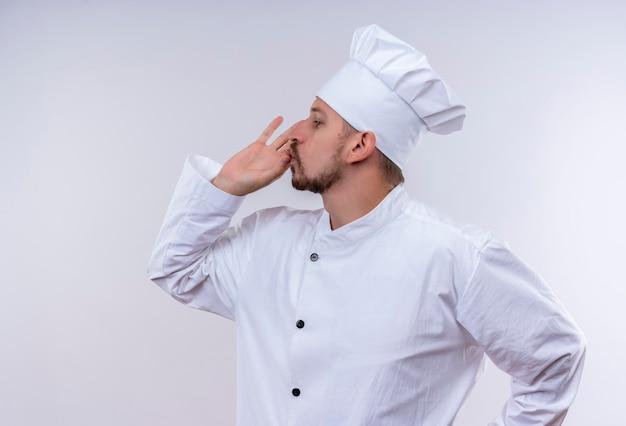 満足しているプロの男性シェフが白い制服を着て調理し、白い背景の上に美味しい立っての兆しを見せている帽子を調理します。