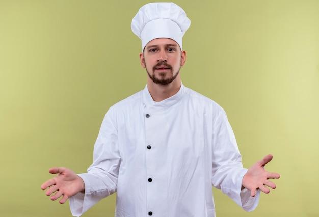 満足しているプロの男性シェフが白い制服を着て調理し、緑の背景の上に立って居心地の良いジェスチャーを作る手を広げて帽子を調理します。