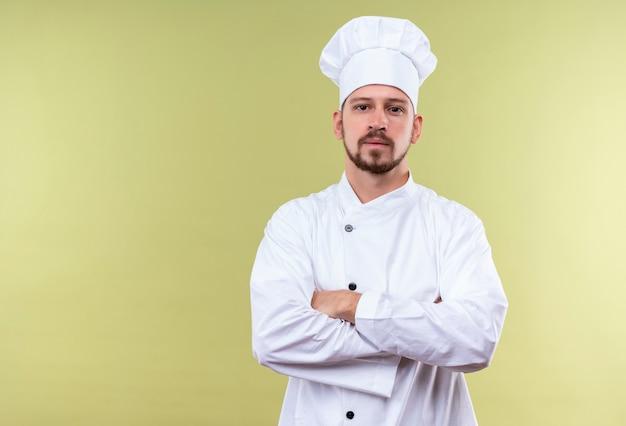 満足しているプロの男性シェフが白い制服を着て調理し、腕を組んで帽子を組んで緑の背景に自信を持って探して
