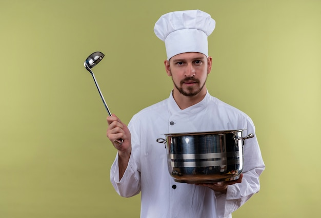 Satisfied professional male chef cook in white uniform and cook hat holding a pan and soup ladle looking at camera with serious face standing over green background