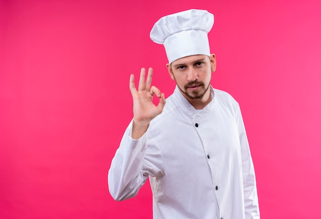 Satisfied professional male chef cook in white uniform and cook hat showing ok gesture looking confident standing over pink background