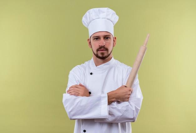 Chef maschio professionista soddisfatto cucinare in uniforme bianca e cappello da cuoco in piedi con le braccia incrociate tenendo il mattarello guardando fiducioso su sfondo verde