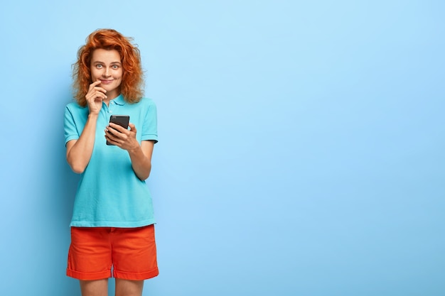 満足した赤毛の女性ブロガーがフォロワーからのコメントをチェックし、新しい出版物を作成します