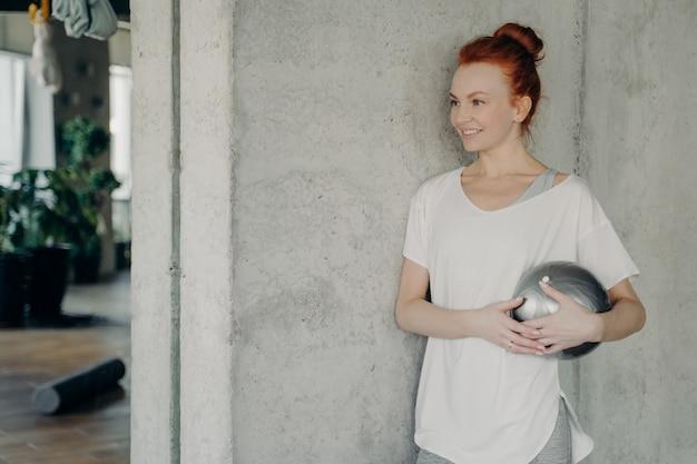 작은 핏볼을 손에 들고 콘크리트 벽에 기대어 서서 옆을 바라보며 웃고 있는 피트니스 스튜디오에서 운동 시간을 즐기고 있는 만족스러운 redhaired 여성. 건강한 라이프 스타일 개념