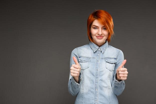 満足している赤毛の女性の親指