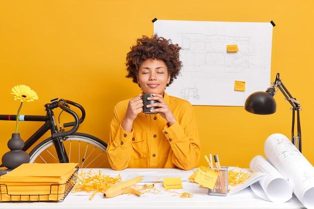 만족 한 편안한 여성 건축가 회사원이 커피 브레이크가 쾌락에서 눈을 감고 냄새가 향기로운 음료가 바탕 화면에서 초안을 그려 스케치를 만듭니다.