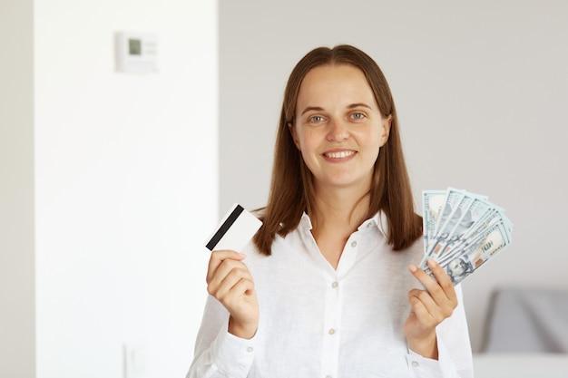 Удовлетворенная богатая молодая взрослая женщина в белой рубашке повседневного стиля, позирует в светлой комнате дома, показывает на камеру кредитную карту и большой поклонник долларовых банкнот, банковское дело.