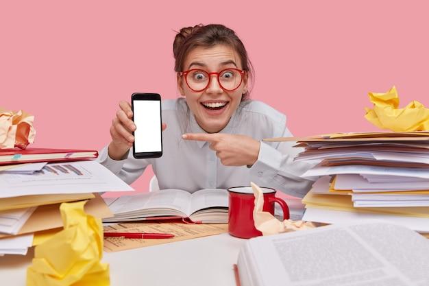 Studentessa soddisfatta con espressione felice, sorriso a trentadue denti, punta al cellulare con schermo vuoto per i tuoi contenuti promozionali, naviga in internet