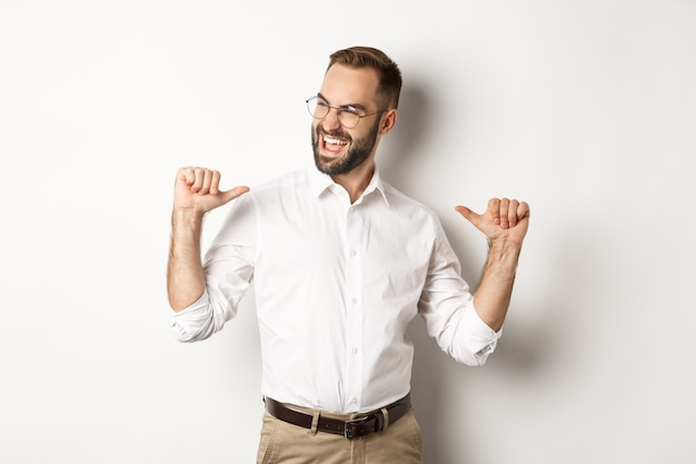 Satisfied and self-assured businessman pointing at himself, standing over white background.