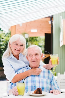 Satisfied senior couple hugging in cafe on terrace enjoying refreshing drink and cake