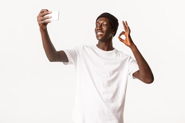 Довольный, улыбающийся молодой афроамериканец в шапочке, делает селфи или видеозвонок через смартфон, демонстрирует жест на автопортрете
