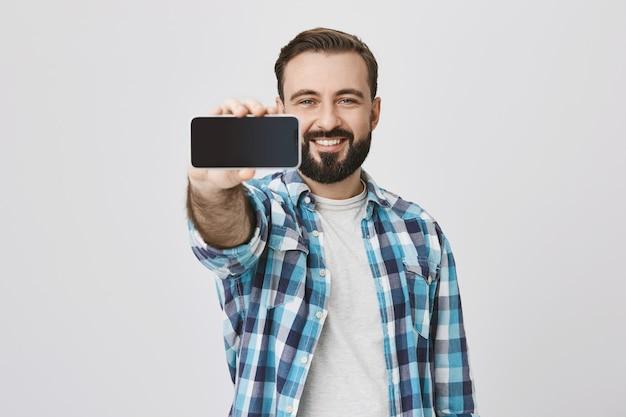 スマートフォンの画面、アプリケーションのプロモーションを示す満足の笑みを浮かべてひげを生やした男