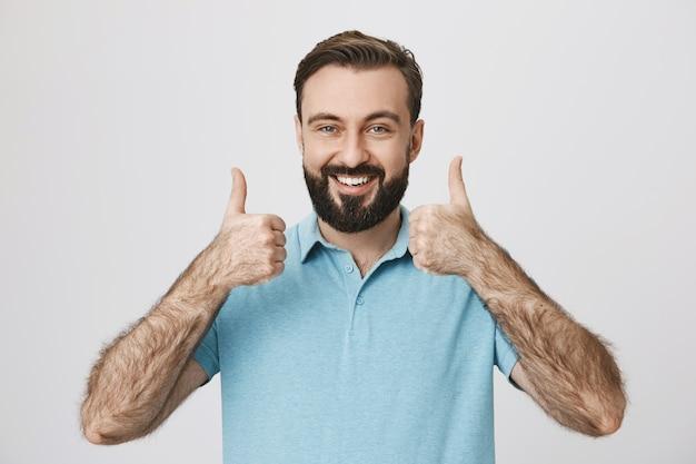 Удовлетворенный улыбающийся бородатый мужчина показывает палец вверх в знак одобрения