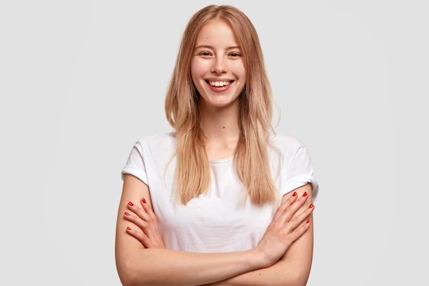 満足のいく笑顔の金髪の若い女性が喜んで表現し、幸せを表現し、カジュアルな白いtシャツを着て