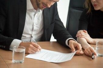 会議のコンセプトで契約に署名のスーツで満足している笑顔の実業家