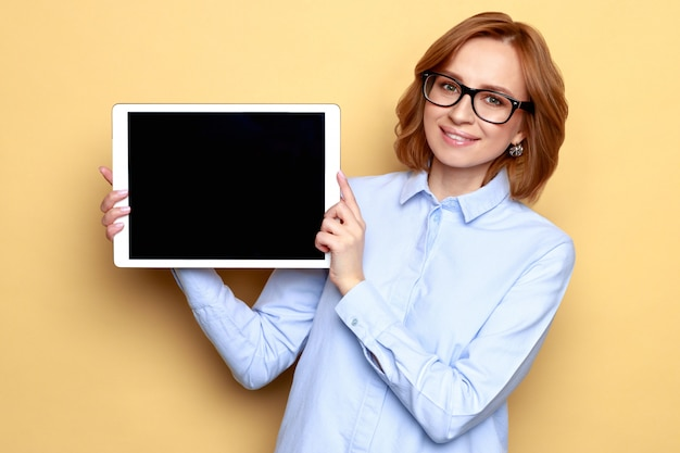 Satisfied smiling businesswoman in blue shirt showing black empty screen with copy space on digital tablet, beige background