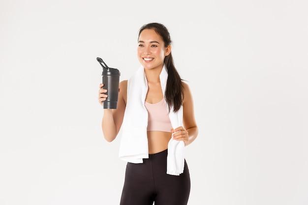 만족 미소, 건강하고 슬림 한 아시아 피트니스 코치, 좋은 훈련, 식수 또는 단백질에 만족하고 수건을 들고있는 소녀.