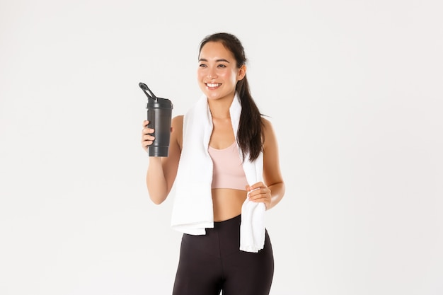 Satisfied smiling, healthy and slim asian fitness coach, girl pleased with good training, drinking water or protein and holding towel.