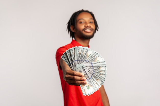 Satisfied smiling man holding out dollar bills at camera, boasting money won in lottery.