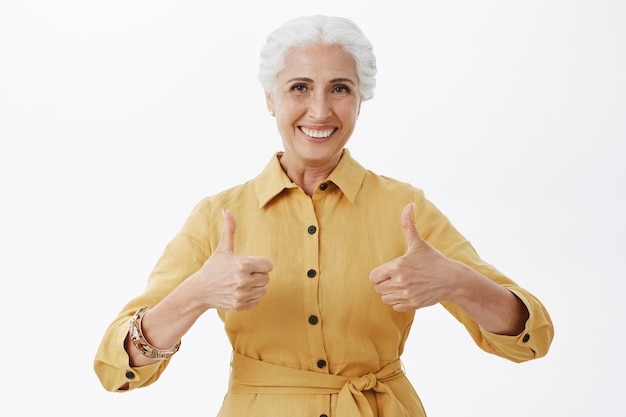 Satisfied smiling senior woman showing thumbs-up in approval, white background