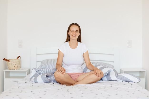 白いカジュアルなスタイルのtシャツとショートパンツを着て、足を組んで明るい寝室のベッドに座って、カメラを見て、朝の幸せを表現して満足している笑顔の若い大人の女の子。