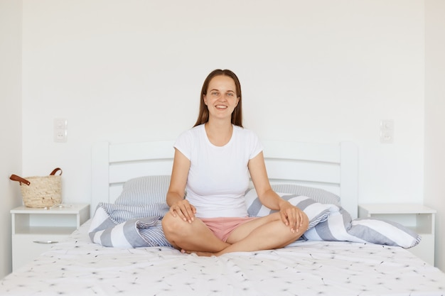 Satisfied smiling young adult girl wearing white casual style t shirt and shorts, sitting on bed in light bedroom with crossed legs, looking at camera, expressing happiness in morning.