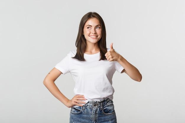 左上隅を見て、承認で親指を立てて示す満足のいく笑顔の若い女性