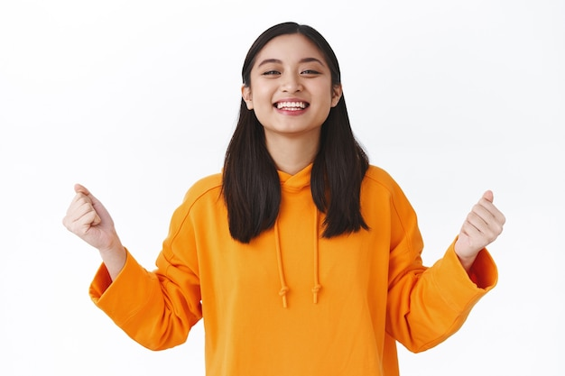 合格したアジアの女子学生の合格試験に満足し、宝くじに当選し、拳ポンプを使って達成感を楽しみ、素晴らしいニュースを祝い、「はい」と言って勝利し、白い壁に立っています。