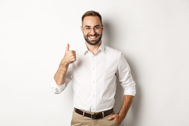 Satisfied successful boss showing thumb up, approve and praise good work, standing over white background.