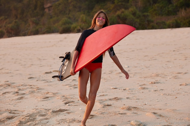 Satisfied surfing young woman holds surfboard, spends summer holidays on tropical island