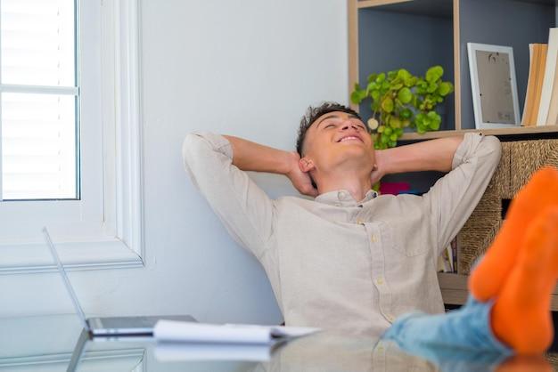 만족스러운 십대는 집에서 노트북으로 일을 끝내고, 손을 들고, 테이블 위에 발을 올려 놓고, 주말 휴가, 편안한 근무일, 스트레스 없음을 기대하며 힘든 하루를 보낸 후 휴식을 취합니다.