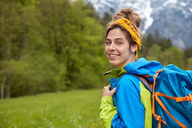 優しい笑顔で満足した旅行者、黄色のヘッドバンドとアノラックを身に着け、大きなリュックサックを運ぶ