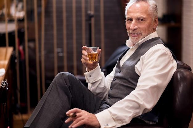 掘り出し物に満足。コニャックガラスと葉巻と革張りのアームチェアに座っているハンサムな身なりのよい老人。