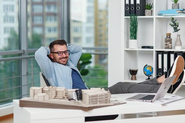 Довольный своим проектом, дизайнер-мужчина сидит в расслабленной позе, закинув ноги на стол в дизайн-студии.