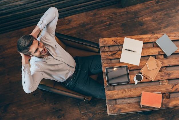 Доволен его работой. вид сверху красивого молодого человека, держащего руки за головой и улыбающегося, сидя на своем рабочем месте