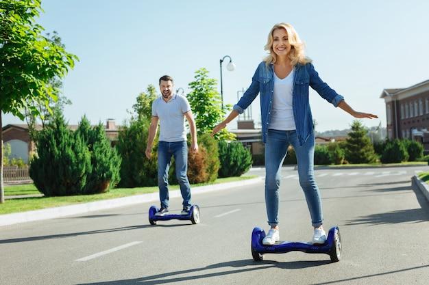 구매에 만족합니다. 즐거운 젊은 남편과 아내가 호버 보드를 타고 행복하게 웃으며 새로운 구매에 만족합니다.