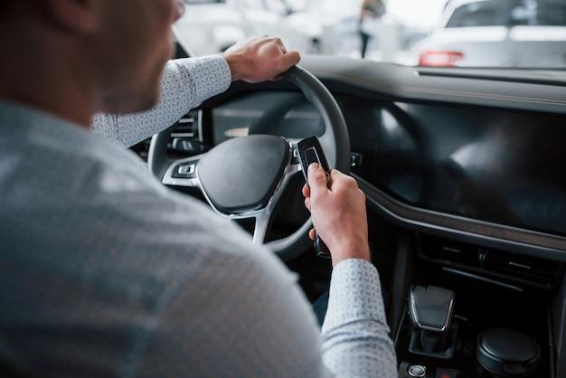 Доволен покупкой. мужчина пробует новую машину в салоне в дневное время. покупка нового автомобиля