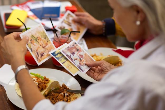 여행에 만족합니다. 멕시코 음식과 함께 카페에서 점심을 먹고 마지막 휴가 사진을 보고 있는 부부.
