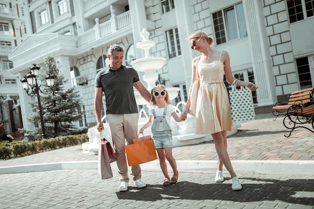 買い物に満足。一緒に買い物をした後、手をつないで買い物袋を持って帰宅する幸せな家族。