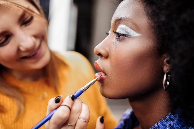Satisfied with work. fair-haired young stylist with black nail polish smiling nicely while putting lip gloss on models lips