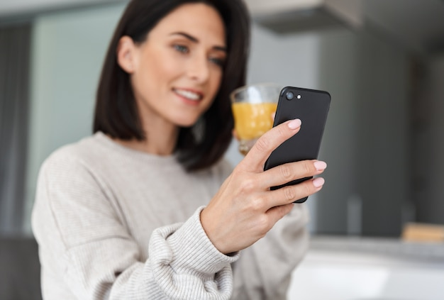 Satisfied woman 30s drinking orange juice and using mobile phone, while resting in bright modern room