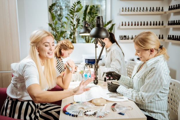 Satisfied woman. blonde-haired stylish beaming woman feeling satisfied looking at her nail art
