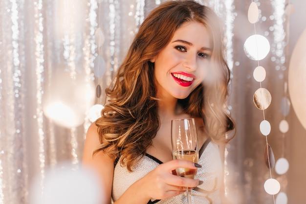 笑顔でお祝いの衣装で満足している女性。シャンパンを飲む巻き毛の女の子のスナップショット
