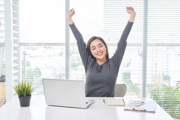 그녀의 머리 뒤에 손으로 편안한 만족된 여자입니다. 퇴근 후 행복한 미소 짓는 직원, 좋은 소식 읽기, 직장 휴식, 간단한 운동을 하는 소녀, 근육 스트레스 해소, 기분