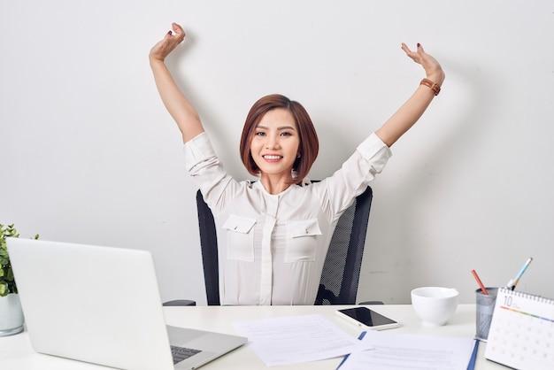 彼女の頭の後ろの手でリラックスして満足している女性。仕事を終えて、良いニュースを読んで、仕事で休憩した後、幸せな笑顔の従業員