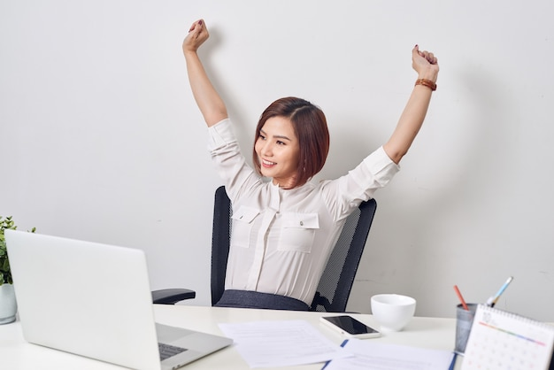 Satisfied woman relaxing with hands behind her head. happy smiling employee after finish work, reading good news, break at work