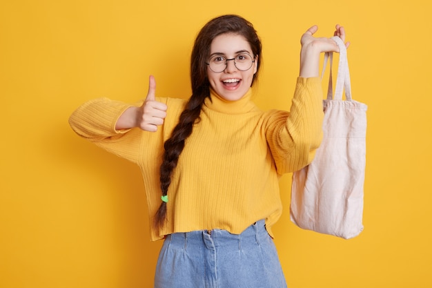 Satisfied woman with long pigtail showing thumb up and holding bag in hand, enjoying her shopping
